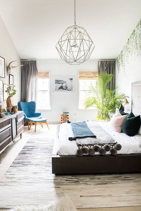 a boho bedroom with a statement tropical plant in the corner that catches an eye