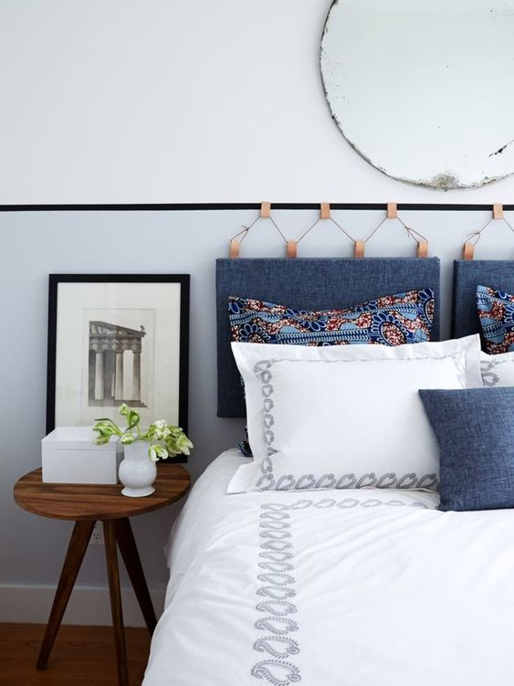 a hanging headboard made of blue denim on amber leather holders and a matchign denim pillow on the bed