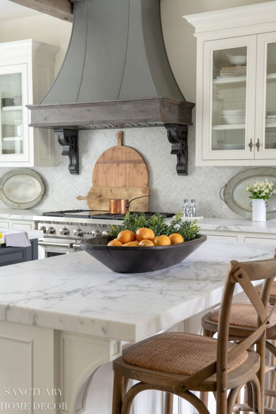 a neutral kitchen with white stone countertops and a vintage metal hood in greys to add chic and color