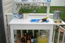 20 a stylish and simple outdoor bar station with glasses, bottles and even a wine cooler