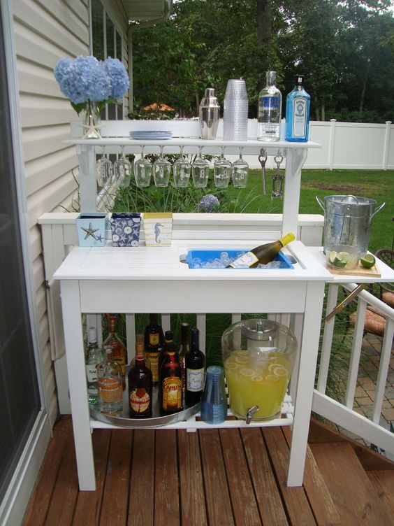 a stylish and simple outdoor bar station with glasses, bottles and even a wine cooler