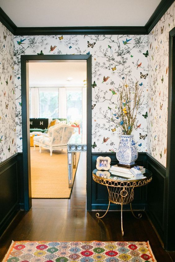 a whimsy entryway with bright flora and fauna wallpaper and chic and refined furniture plus a rug