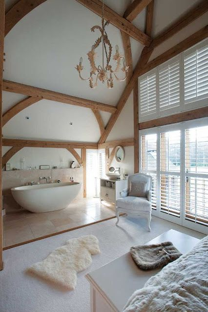 a gorgeous refined space with wooden beams and a bathtub zone done with large scale tiles