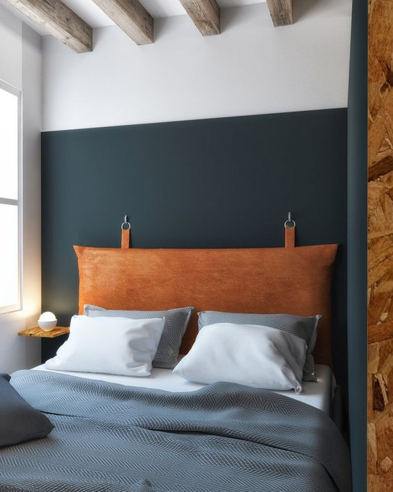 a hanging headboard of amber leather looks soft and textural and adds interest to the space