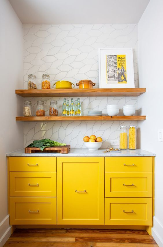 a tiny kitchen with bright yellow cabinets, all whites and wooden shelves over the cabinets