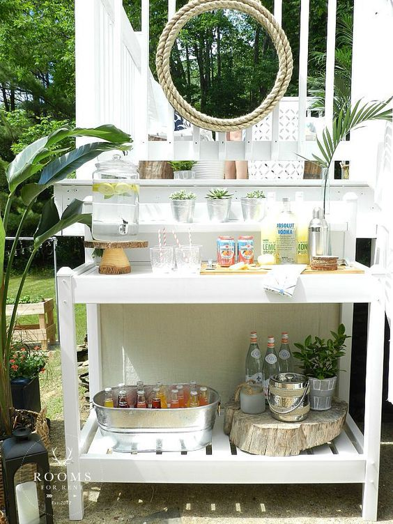 a white home bar station with various drinks, a cooler of a bucket and potted succulents and greenery