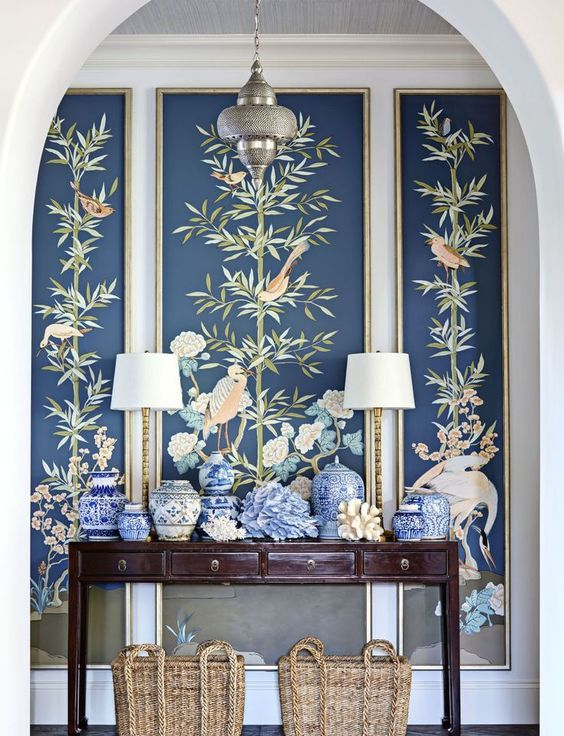 an entryway with a console, blue vases, lamps and dark flora and fauna wallpaper for a statement