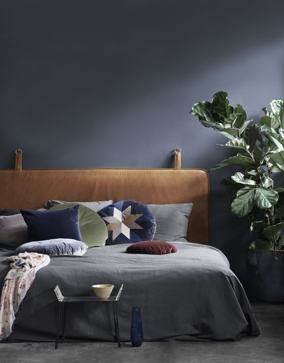 a moody bedroom in black refreshed with a potted plant, bright pillows and a leather hanging headboard for a statement
