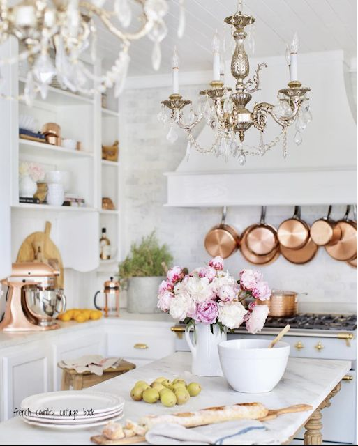 a stylish modern white kitchen with two vintage chandeliers that add chic and beauty to the space