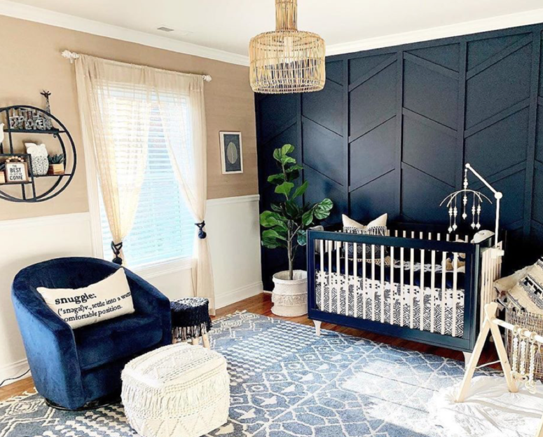 an elegant nursery with a black 3D geometry accent wall, a matching crib and a navy chair to create a cohesive look