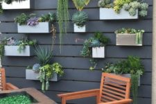 23 a black wooden plank wall with concrete and metal planters attached and lots of succulents and cacti
