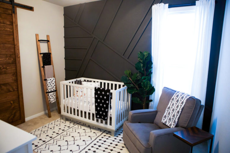 a boho nursery with a black geometric wall and a grey chair to match looks very bold and modern