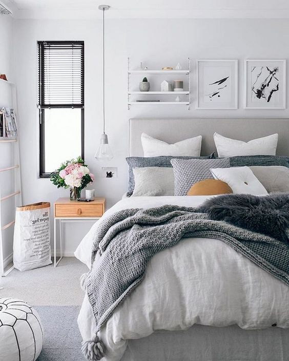 a contemporary bedroom with an arrnagement of throws on the bed and textural blankets