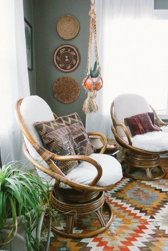 a duo of wooden papasan swivel rockers with white futons and boho and folksy pillows
