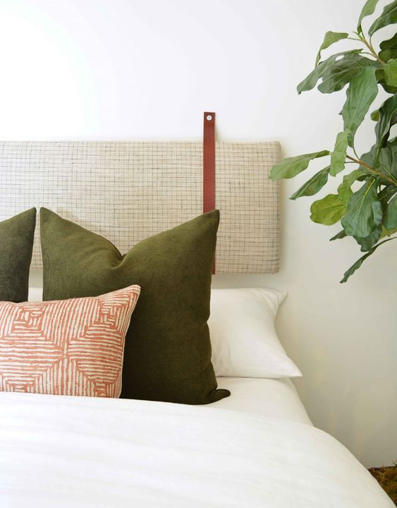 a neutral yet printed headboard of a long cushion on leather straps looks cool and bold