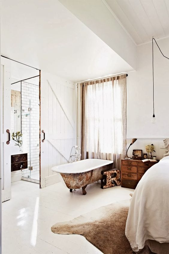 a rustic vintage bedroom with a shabby rust-touched bathtub for a vintage feel