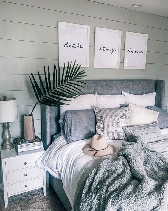 a boho bedroom in neutrals with an upholstered bed and some matching throws but of different fabric