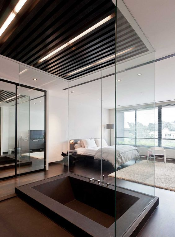 a contemporary bedroom with a large dark metal sunken bathtub separated with glass to avoid splashes on the floor