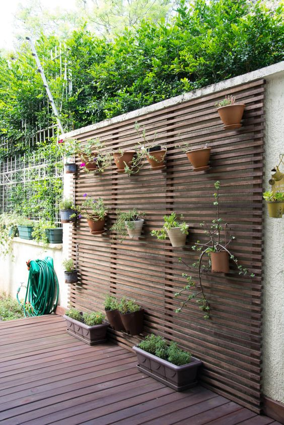a dark wooden plank wall with various planters attached is a simple idea to enliven your space