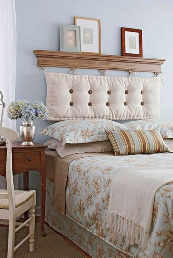 a vintage-inspired bedroom in pastel blues, tan and creamy, with a cushion headboard hanging on a small shelf