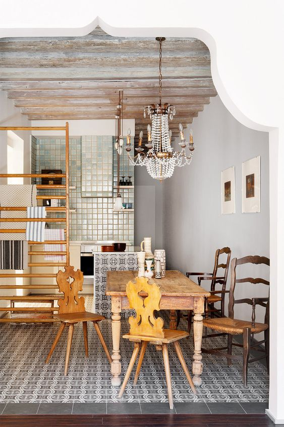 an eclectic space with printed tiles, a wooden dining set and a gorgeous crystal vintage chandelier over the space