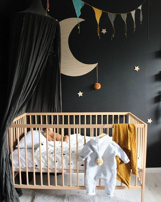 a cute celestial nursery with a black statement wall and a black cnaopy over the crib to make the space peaceful