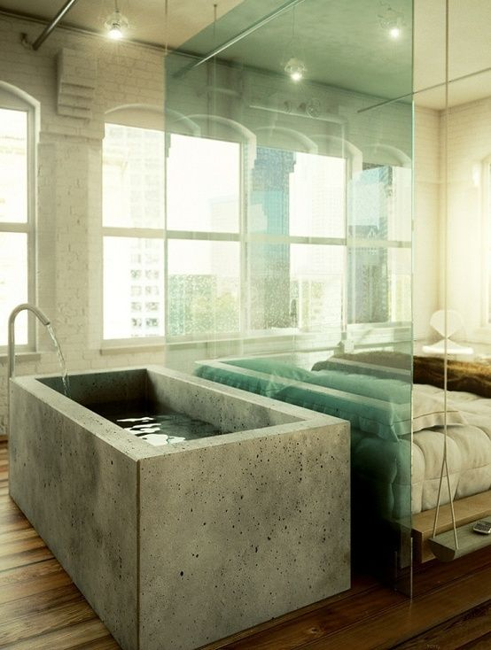 a industrial bedroom with a concrete bathtub separated with a glass divider from the bed