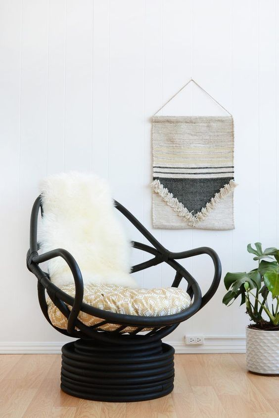 a modern black wooden papasan swivel rocker with neutral upholstery and faux fur