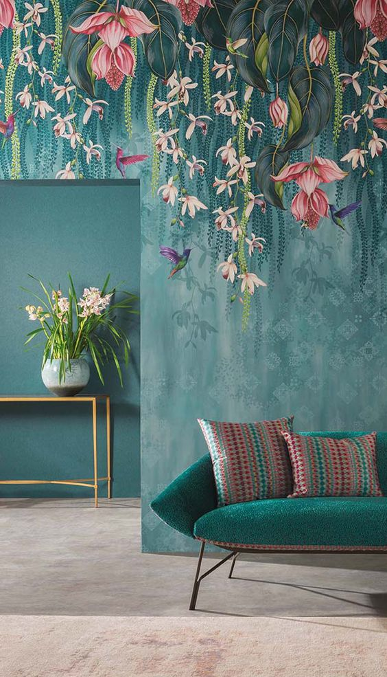 a moody space with catchy flora and fauna wallpaper that imitates hanging blooms over the furniture