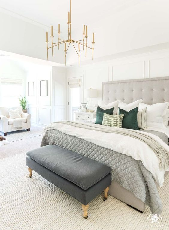 a neutral bedroom with a grey statement bed, an arrangement of pillows