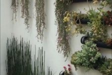 25 a wall with black metal planters with greenery and bright blooms and concrete planters with grasses