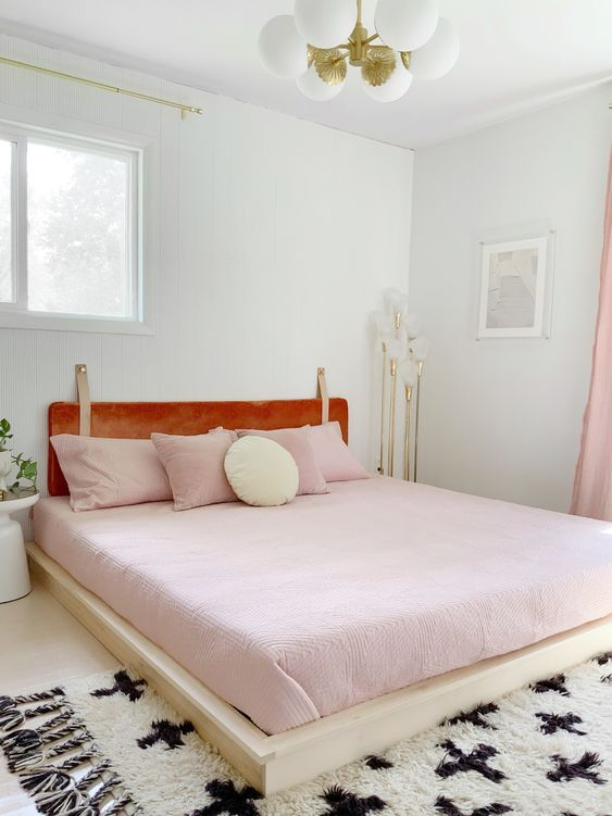 a welcoming girlish bedroom with pink bedding and an amber leather headboard hanging