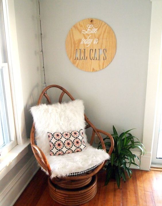 a boho nook with a wooden papasan swivel rocker with faux fur and a bright pillow