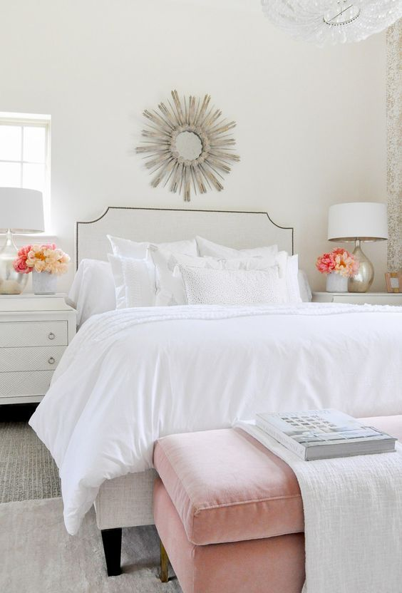 a chic and airy bedroom with a white bed and an arrangement of white pillows but of various fabrics