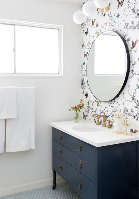 a neutral bathroom with a black vanity, floral and fauna wallpaper and a round mirror for a bold look