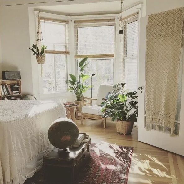 a biophilic boho bedroom with potted plants, lots of natural light and natural textiles plus rugs