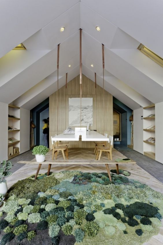 a biophilic dining space with plenty of natural wood in decor, some potted greenery and a large pompom rug that imitates moss