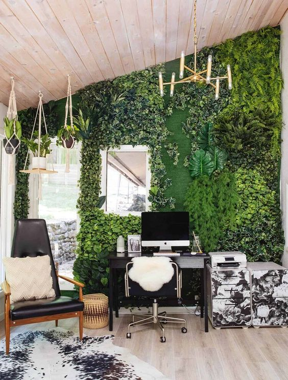 a biophilic home office with a greenery wall and potted plants hanging from above looks very fresh