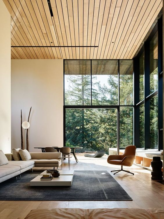 a biophilic living room with glazed walls to maximize the views and natural light and a wooden ceiling and floor