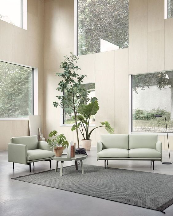 a biophilic living room with lots of windows to maximize the views and light and some potted plants inside