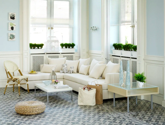 a biophilic living room with plenty of natural light and potted greenery plus natural materials in furniture design