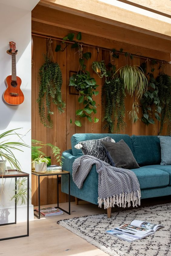 a biophilic living room with potted plants suspended over the sofa to the natural wooden wall