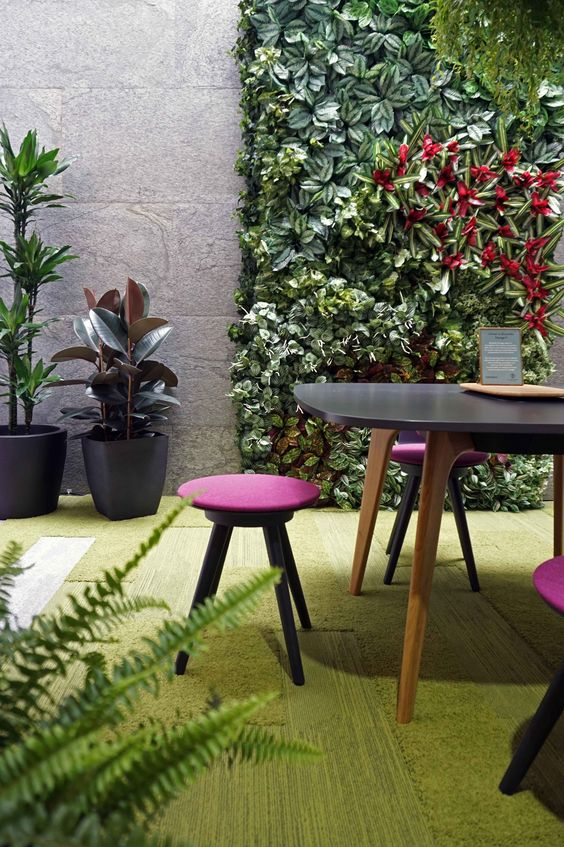 a biophilic space with a greenery wall, a rug that imitates moss and grass, potted plants for a fresh feel