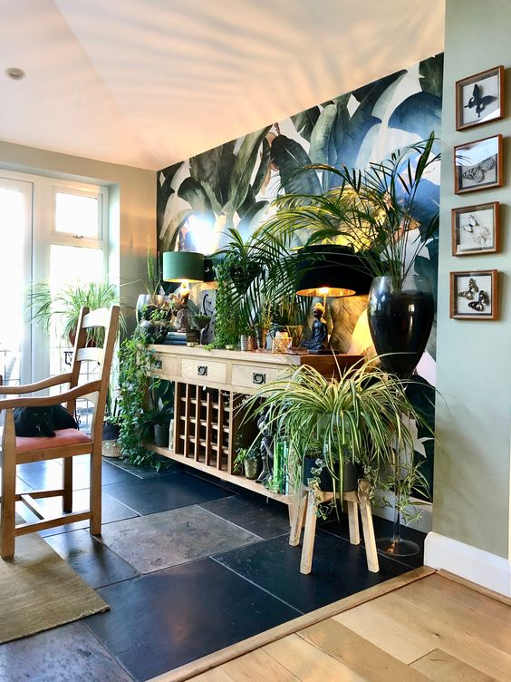 a biophilic space with potted greenery and plants, with a tropical print wall and wooden furniture