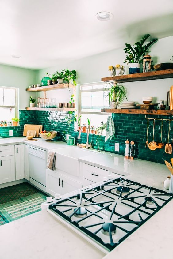 a boho kitchen with white cabinets, a bright green tile backsplash, lots of greenery and green rugs