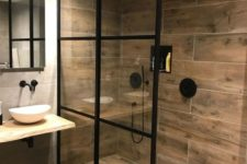 a bold contemporary bathroom with wood look tiles, a wooden vanity and black framing for a dramatic touch