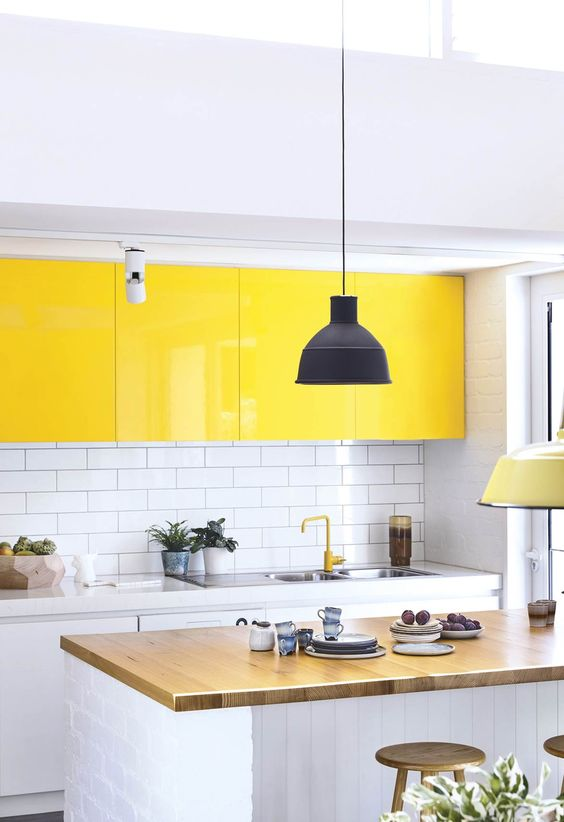 a bold contemporary kitchen done in white, with bright yellow upper cabinets, a wooden countertop and a white subway tile backsplash