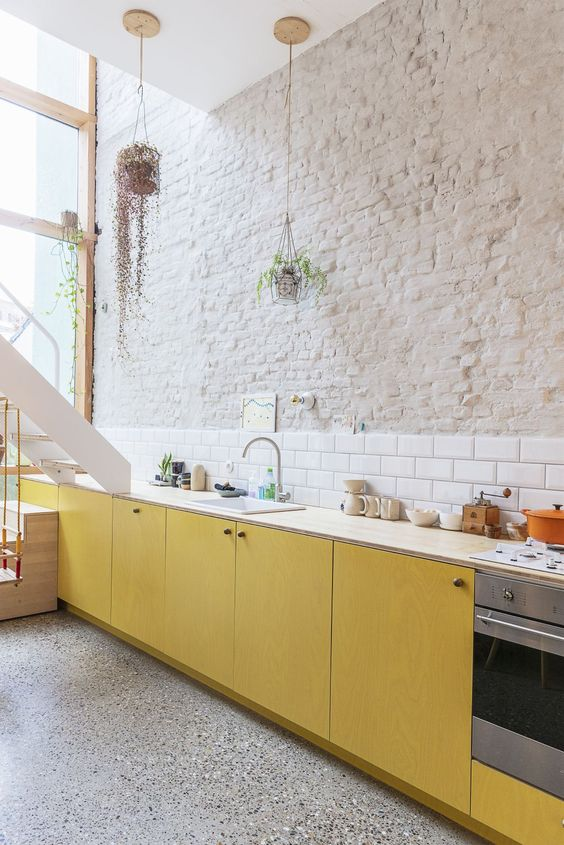 a bold contemporary kitchen with yellow plywood cabinets, neutral countertops, a white subway tile backsplash and a brick wall