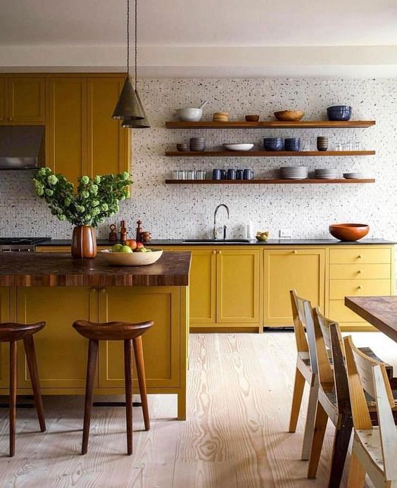 a bold kitchen with mustard cabinets, wooden countertops, a white tile backsplash and touches of wood here and there