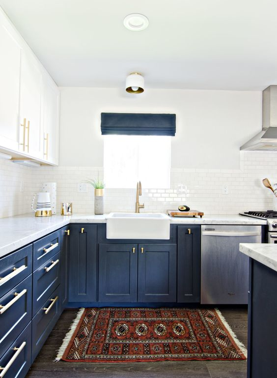 a bold kitchen with navy lower cabinets, white upper ones, gold touches, a bold boho rug and navy shades